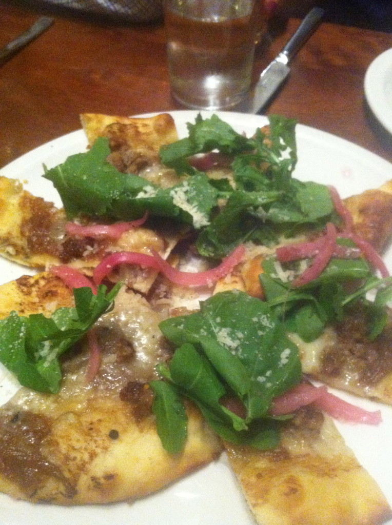 Flatbread of spicy fennel sausage, pickled onions, and spinach